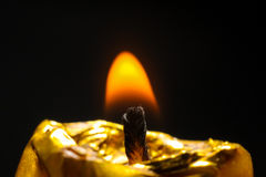 Golden candle burn on black background flame Stock Photo