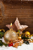 Golden candle and christmas decoration in snow Royalty Free Stock Image