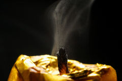 Golden candle macro dust after breath black background. Golden candle macro dust black background Royalty Free Stock Image