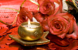 Golden candle with red roses Stock Photos