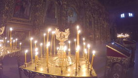 The golden candleholder. KIEV, UKRAINE - JANUARY 4, 2017: The candleholder with burning candles next to iconostasis of St Michael Golden Domed Cathedral, on stock video