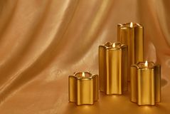 Golden candlelit background. Four golden candles with different sizes on a golden background with copy-space stock photo