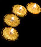 Golden candles on a black background. Stock Image