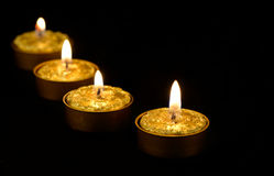 Golden candles on a black background. Stock Photos