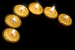 Golden candles on a black background. Royalty Free Stock Image