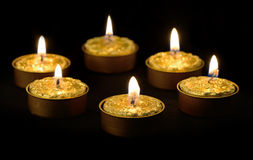 Golden candles on a black background. Royalty Free Stock Photos