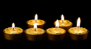Golden candles on a black background. Stock Photography