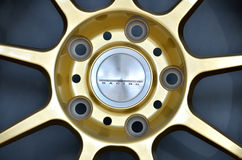 Golden car rim. Close-up golden car rim for sports car against grey background Royalty Free Stock Images