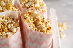 Golden caramel popcorn in pink paper bags in a white wooden box. stock photography