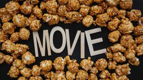 Golden caramel popcorn closeup. Background of popcorn. Wooden letters Movie. Golden caramel popcorn closeup. Background of popcorn. Snacks and food for a movie royalty free stock images