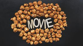 Golden caramel popcorn closeup. Background of popcorn. Wooden letters Movie. Golden caramel popcorn closeup. Background of popcorn. Snacks and food for a movie stock photo