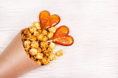 Golden Caramel popcorn in a paper cup and lollipops in the shape of a heart. Royalty Free Stock Photos