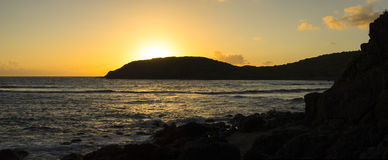 Golden Caribbean sunrise. Panoramic of glowing sun rising behind Punta de Molinos casting reflections on Caribbean Sea on Isla Culebra, Puerto Rico Stock Photography