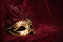 Golden carnival mask with red feathers on a red velvet theater c. Golden venetian carnival mask with red feathers seen from the side on a draped red velvet stock images