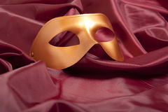 Golden carnival mask. On red satin background Royalty Free Stock Photography