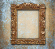 Golden carved antique frame on grunge worn wall stock photo
