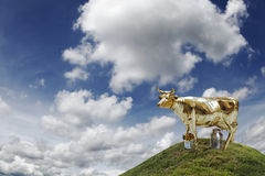 Golden Cash Cow. A golden cow on top of a grassy hill against a cloudy blue sky, for the concept of financial cash cow Royalty Free Stock Photography