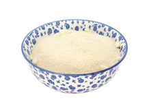 Golden caster sugar in a blue and white china bowl. Golden caster sugar in a blue and white porcelain bowl with a floral design, isolated on a white background stock photo