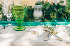 Golden celtic wedding rings on white wooden table. Closeup of golden celtic wedding rings, green glass, knife and fork on white wooden table,  focus on rings Royalty Free Stock Image