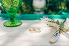Golden celtic wedding rings on white wooden table. Closeup of golden celtic wedding rings, green glass, knife and fork on white wooden table,  focus on rings Stock Photos