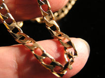 Golden chain. Gold chain on fingers - macro picture on a black background stock images