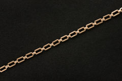 Golden chain on black felt background. Antique golden chain on black felt textured background Royalty Free Stock Photo