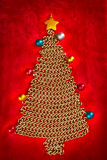 Golden chain Christmas tree on red Stock Photography