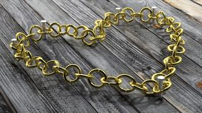 Golden chain in shape of heart Stock Photo