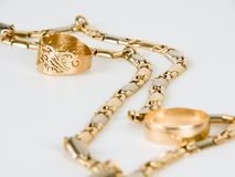 A golden chain and two rings. A golden chain and two wedding rings royalty free stock image