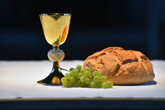 Golden chalice, bread and grapes. Beautiful golden chalice with grapes and bread on the altar Royalty Free Stock Image