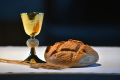 Golden chalice, bread and grapes. Beautiful golden chalice with grapes and bread on the altar Royalty Free Stock Images