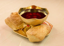 Golden chalice with red wine and bread broken into on a marble t Royalty Free Stock Image