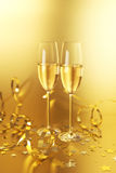 Golden Champagne. Two champagne flutes on a golden background stock photos