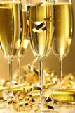 Golden champagne sparkle. With fluted glasses and party ribbons Royalty Free Stock Images