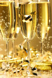 Golden champagne sparkle. With fluted glasses and party ribbons Stock Image
