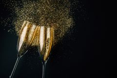 Golden champagne toast. Two glasses of champagne toasting with golden glitter on a dark background. Flat lay. Night of celebration concept royalty free stock images