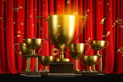 Golden champion trophies and confetti on red royalty free stock photo