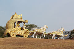 A golden chariot with the god Krishna and horses stock photography