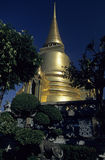 Golden chedi. In the King's palace area of Bangkok, the capital of Thailand, against dark blue sky stock image