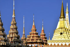 Golden chedis under blue sky, Thailand Royalty Free Stock Images