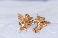 Golden cherubs playing violin in snow. Conceptual image of christmas or purity religion golden cherubs playing violin in snow stock photography