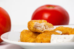 Golden chicken nuggets on plate with tomatoes Stock Photography