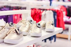 Children sneakers on the shelves in the store stock photos