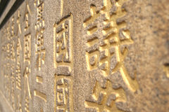 Golden Chinese Characters Carved on Stone Wall. Golden Chinese Characters Stock Photo