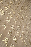 Golden Chinese Characters Carved on Stone Wall. Golden Chinese Characters Stock Images