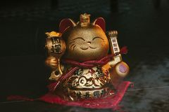 A golden chinese lucky cat with its left paw raised, on a rustic wooden surface stock photography
