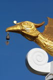 Golden Chinese swan Feng sculpture with a bell. Golden Chinese swan Feng sculpture on a roof of a temple stock photo