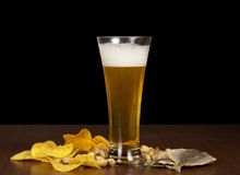 Golden chips, pistachios, salty fish and beer Stock Photo