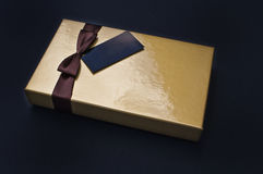 Golden chocolate box closed with black label Royalty Free Stock Photography