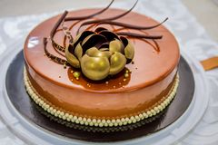 Golden chocolate cake with flower and pearls Stock Image